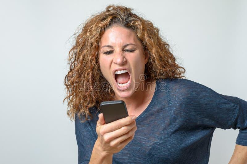 Gritaria irritada da jovem mulher em seu móbil fotografia de stock royalty free