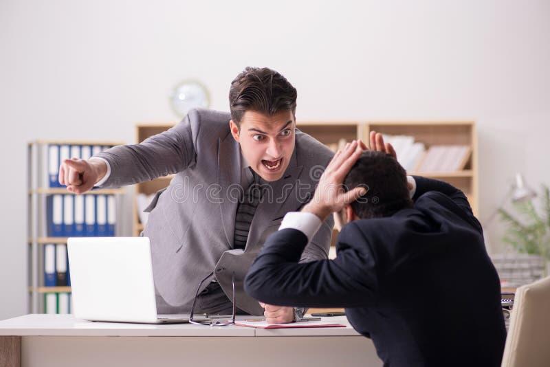A gritaria irritada do chefe em seu empregado foto de stock royalty free