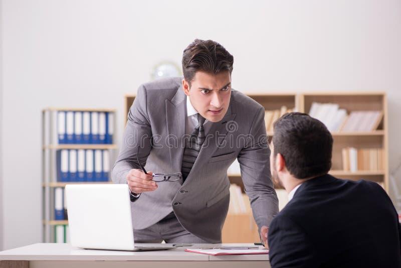 A gritaria irritada do chefe em seu empregado imagem de stock royalty free