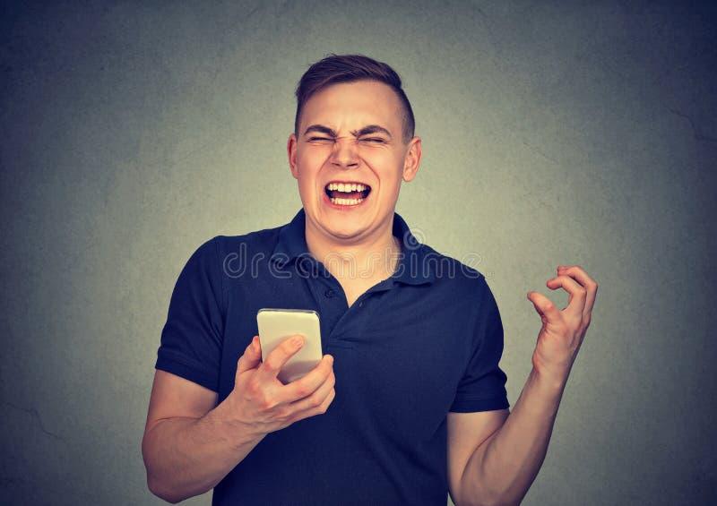 Gritaria irritada do homem em seu telefone celular, irritado com o serviço mau de má qualidade do smartphone fotos de stock royalty free