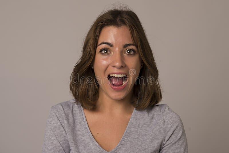 Griterío atractivo y hermoso joven de la mujer emocionado y feliz en choque agradable y la sorpresa que muestran el positivo y la imagen de archivo
