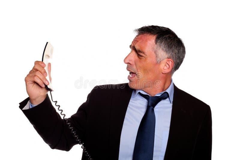 Griterío ejecutivo enojado en el teléfono foto de archivo