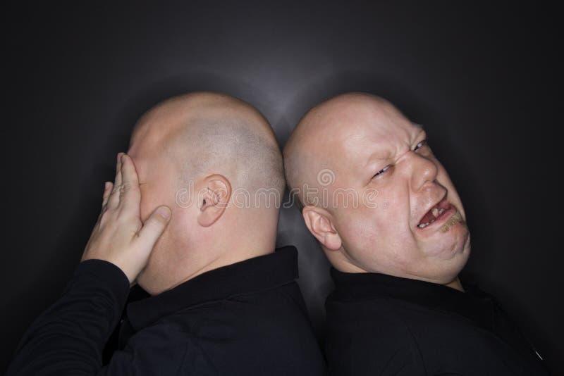 Griterío gemelo calvo de los hombres. fotos de archivo