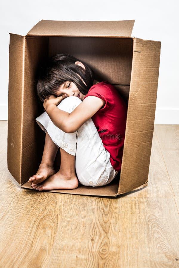 Griterío triste, niño cansado hunched en la pequeña caja para el refugio fotografía de archivo