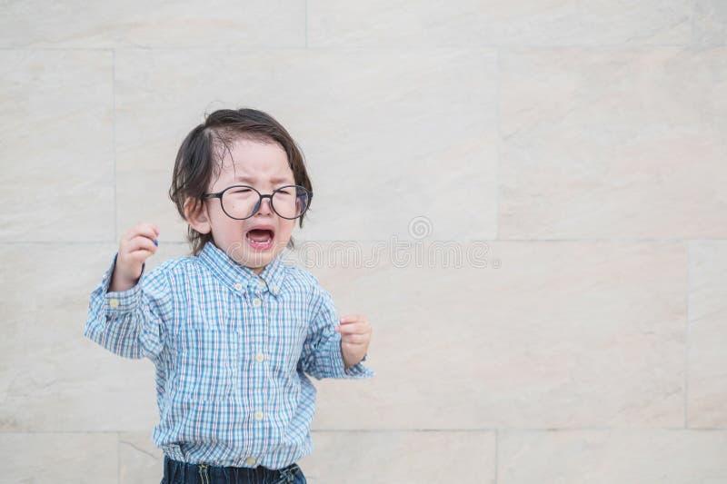 Grito asiático triste del niño del primer porque él quiere algo en el fondo texturizado de mármol de la pared de piedra con el es foto de archivo libre de regalías