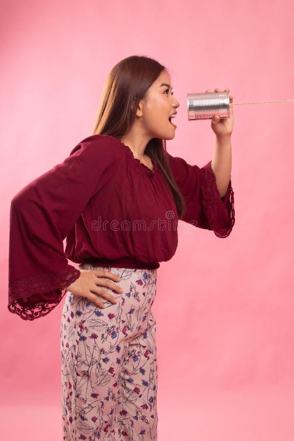 Grito asi?tico joven de la mujer con el tel?fono de la lata imagen de archivo libre de regalías