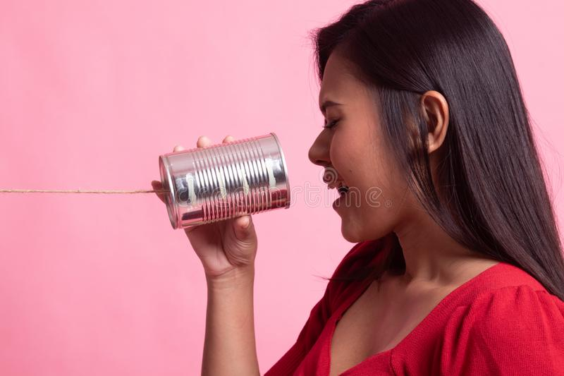 Grito asi?tico joven de la mujer con el tel?fono de la lata foto de archivo