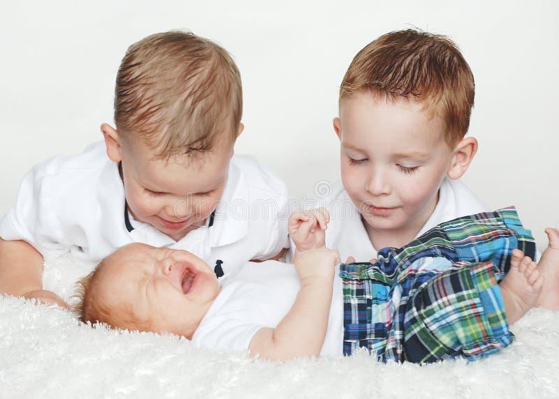 Grito del bebé del reloj de dos muchachos imagen de archivo