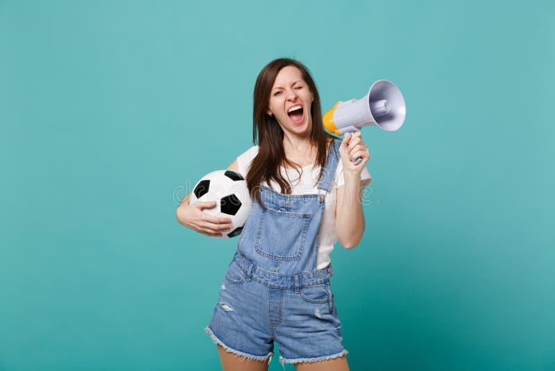 Grito del fanático del fútbol de la muchacha del centelleo en equipo preferido de la ayuda del megáfono con el balón de fútbol ai fotografía de archivo libre de regalías