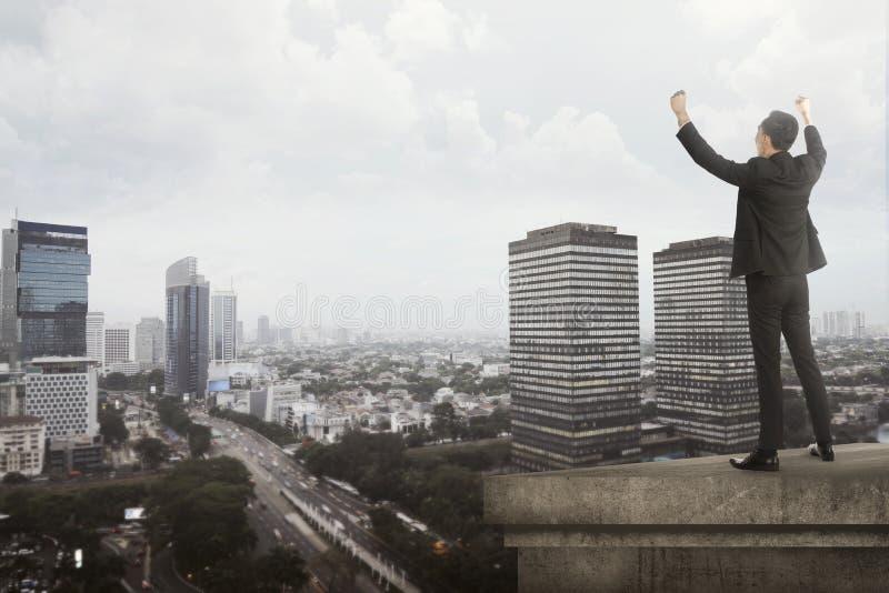 Grito del hombre de negocios en el tejado del edificio fotos de archivo