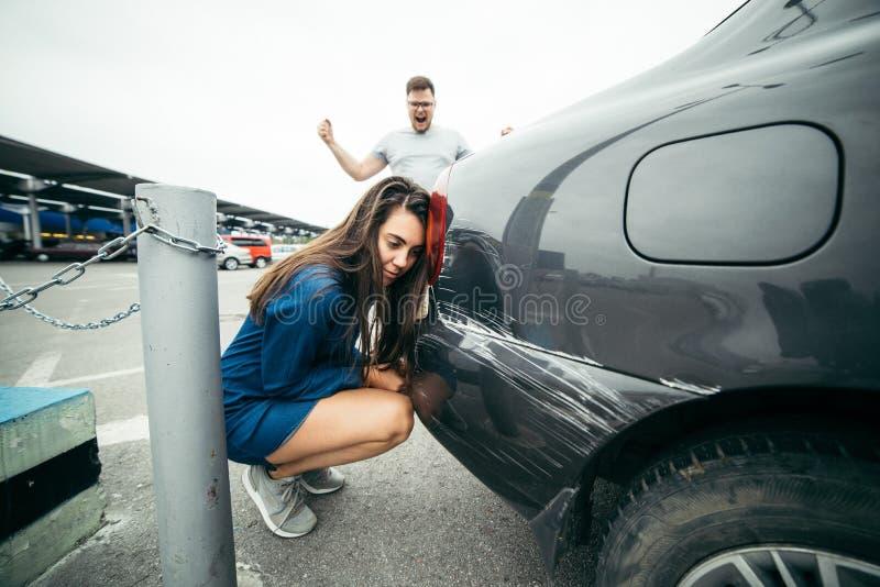 Grito del hombre en mujer debido al coche rasguñado imagenes de archivo