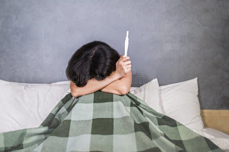 Grito deprimido e desesperado novo da mulher ou do adolescente e resultado positivo dos testes assustado no teste de gravidez ape foto de stock