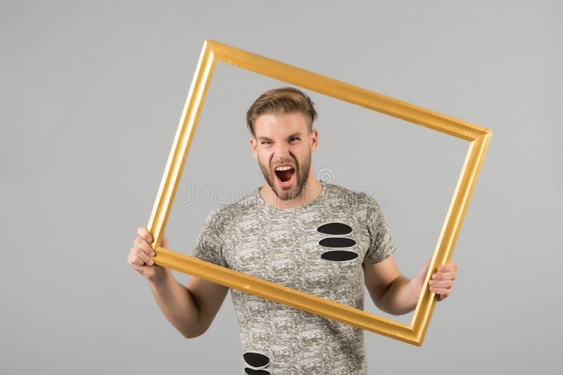 Grito do homem com moldura para retrato no fundo cinzento Macho irritado com quadro de madeira da foto da posse da barba Indivídu fotos de stock