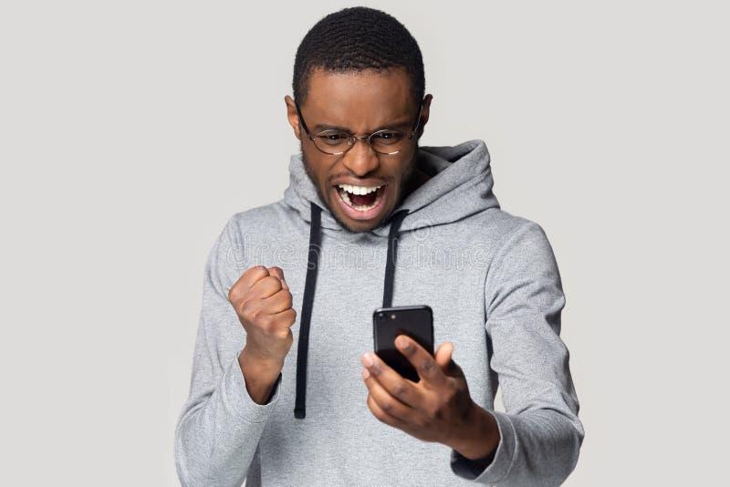 Grito emocionado del smartphone del control del hombre negro wining en línea foto de archivo libre de regalías