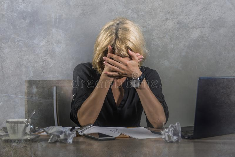 Grito frustrante e forçado novo da mulher de negócio triste na mesa de escritório que trabalha com o laptop oprimido pelo workl d fotos de stock royalty free