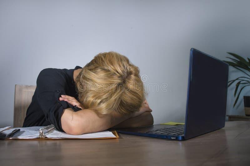 Grito frustrante e forçado novo da mulher de negócio triste na mesa de escritório que trabalha com o laptop oprimido pelo workl d imagens de stock