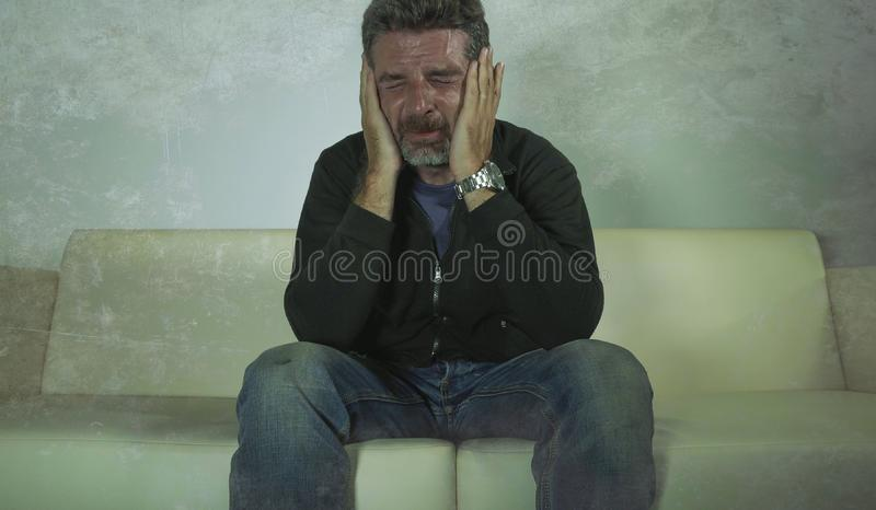 Grito obscuro deprimido e triste atrativo novo do sofá do homem em casa perdido em crise e em depressão da ansiedade do sofriment foto de stock