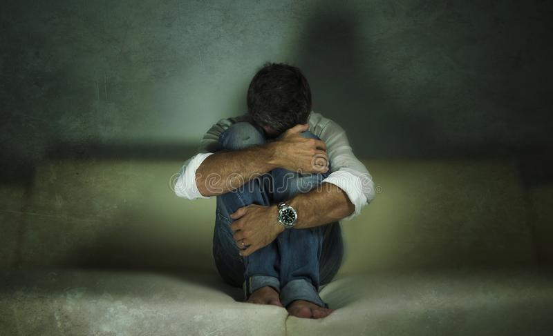 Grito obscuro deprimido e triste atrativo novo do sofá do homem em casa perdido em crise e em depressão da ansiedade do sofriment imagens de stock