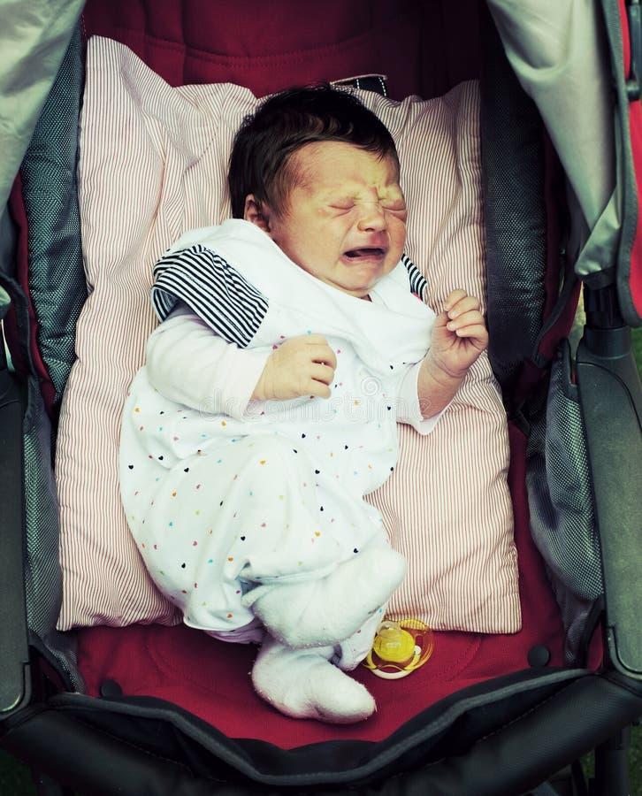 Grito recém-nascido em seu carrinho de criança imagem de stock royalty free