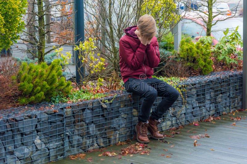 Grito triste do menino do adolescente exterior, cobrindo sua cara com o si das mãos fotos de stock