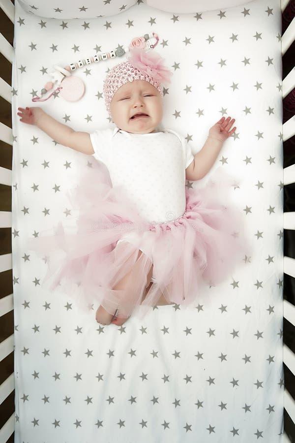 Gritos del bebé en cama con una falda rosada mullida Niño caprichoso opinión superior gritadora del bebé fotos de archivo libres de regalías
