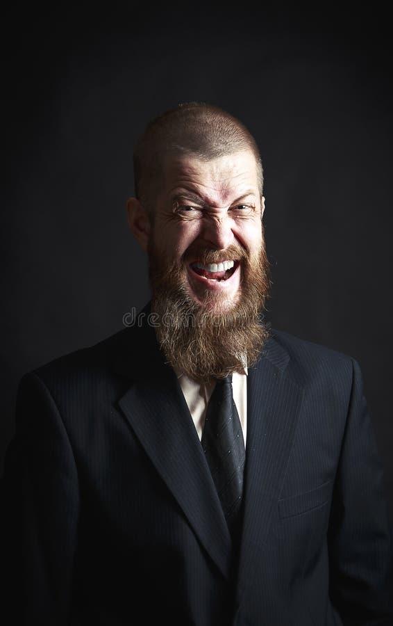 Gritos del hombre con la barba en un fondo negro, retrato foto de archivo