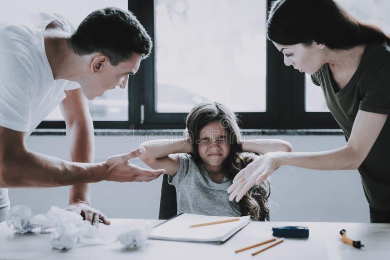 Gritos enojados de los padres en la muchacha mientras que el hacer de la preparación fotos de archivo libres de regalías