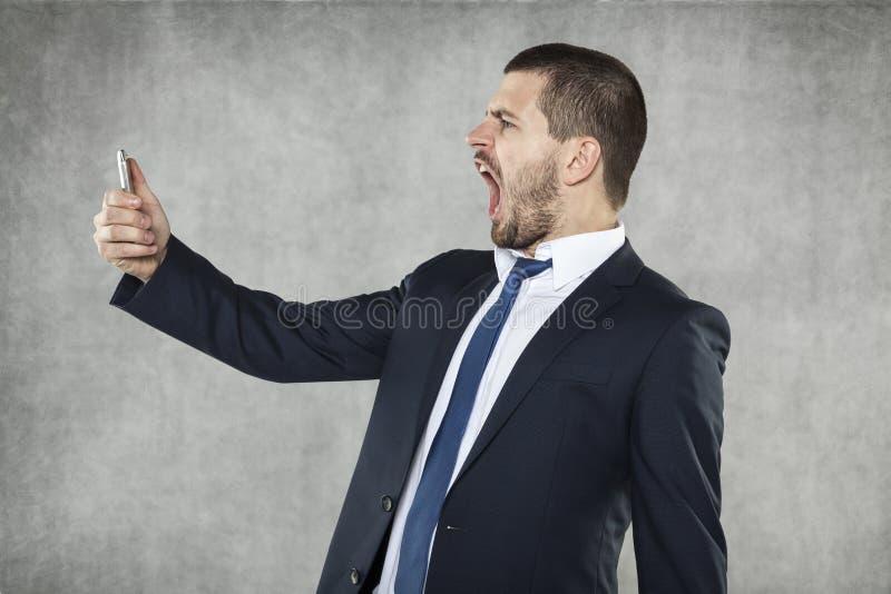 Gritos irritados do homem de negócio fotografia de stock