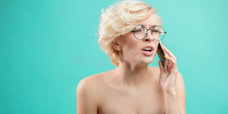 Gritos louros atrativos irritados da mulher ao falar no telefone fotografia de stock royalty free