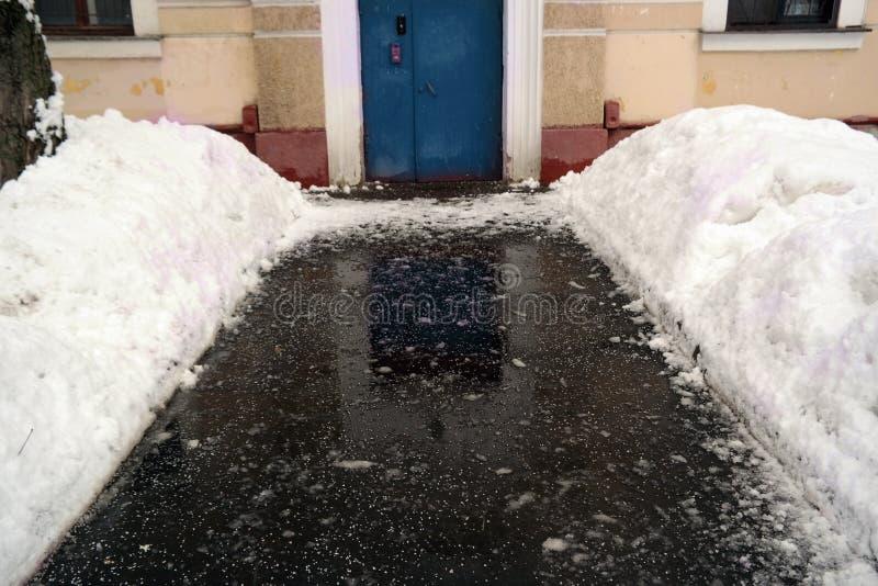 Gritting salt on asphalt. In front of a door entrance, winter scene stock photo