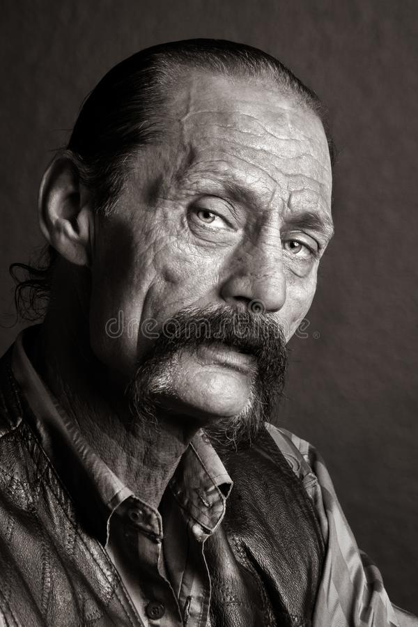 Gritty Looking Biker Man with Horseshoe Mustache and Black Leather Jacket stock photography