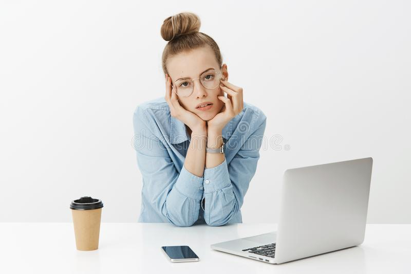 Grl hates her job being bored and sleepy leaning head on table looking indifferent and drained at camera, feeling royalty free stock image