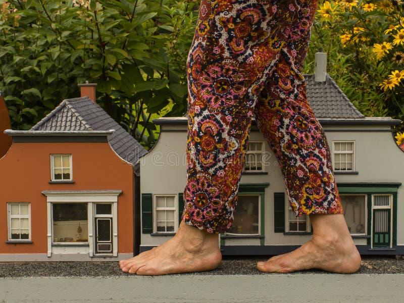 Groß bezahlt und kleine Häuser Ungewöhnliche Ansicht Gulliver in der Stadt stockfotografie