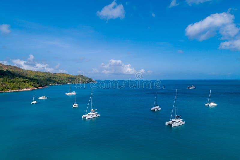 Großartige Vogelperspektive einiger Yachten und kleiner Boote, die auf ein Meer des freien Raumes und des Türkises, Seychellen im stockfotografie