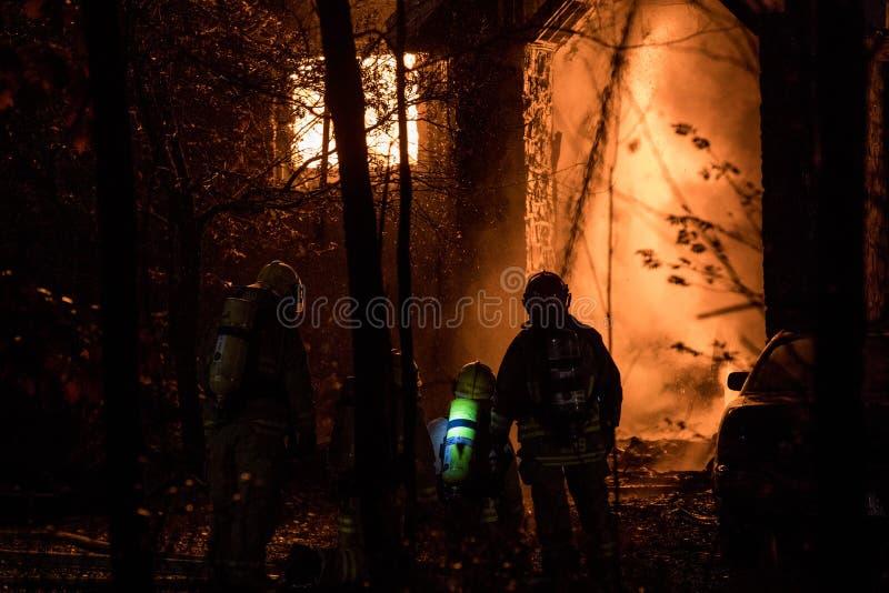 Großartiger Hausbrand, Feuerwehrmänner benutzen Schlauch im Schatten lizenzfreies stockbild