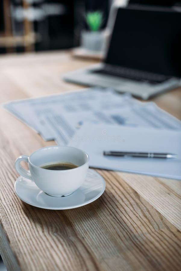 Großaufnahme der Kaffeetasse, der Papiere und des Laptops lizenzfreies stockfoto
