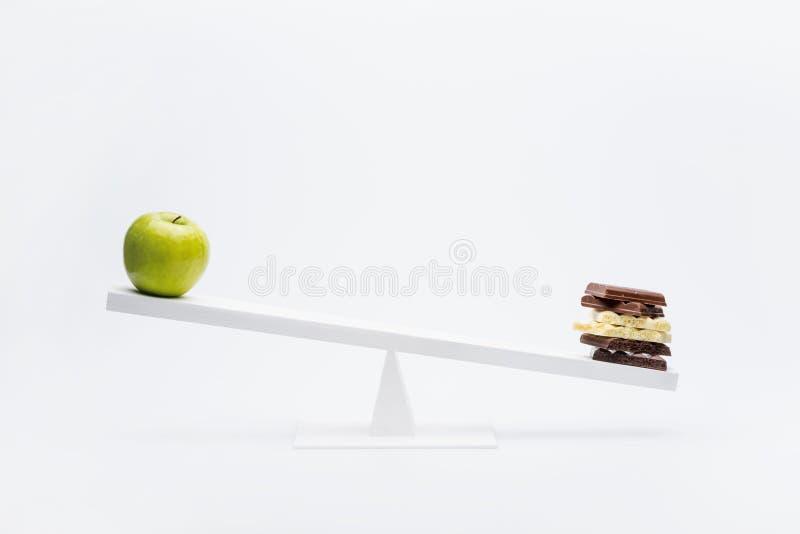Großaufnahme des Apfels und der Schokolade, die auf ständigem Schwanken balancieren stockbild