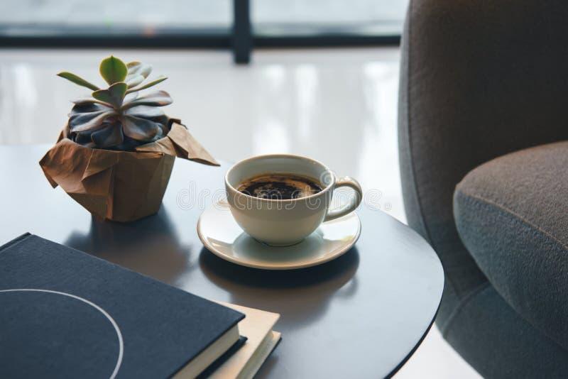 Großaufnahme des grünen Succulent, des Tasse Kaffees und der Bücher lizenzfreie stockbilder