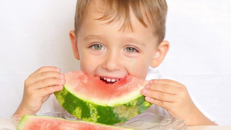 Großaufnahme des netten kleinen Jungen, der am Tisch auf der Küche sitzt Mann, der ein Stück hält und eine Wassermelone - 1 isst lizenzfreie stockfotos