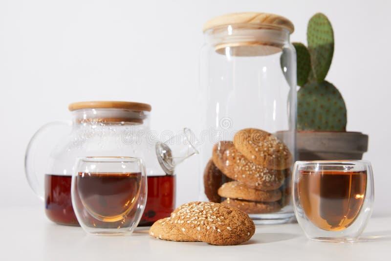 Großaufnahme des Tees in den Gläsern, in den geschmackvollen Plätzchen, in der Teekanne und im Kaktus im Topf auf Grau stockfotos