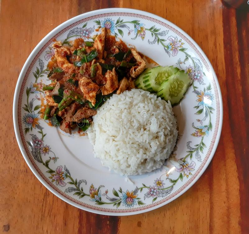 Großaufnahme, Draufsicht der thailändischen Nahrung, angebraten mit Curry-Paste, Huhn und Reis in einem Teller mit köstlichem Gem lizenzfreie stockfotografie