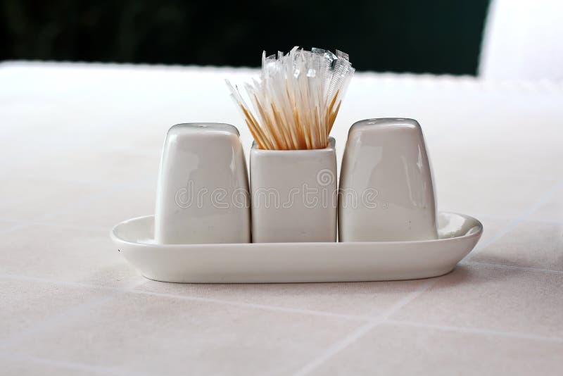 Großaufnahme eines Satzes Schalen für Gewürze, Salz, Pfeffer und Zahnstocher, stehend auf einer weißen Tabelle stockfotografie