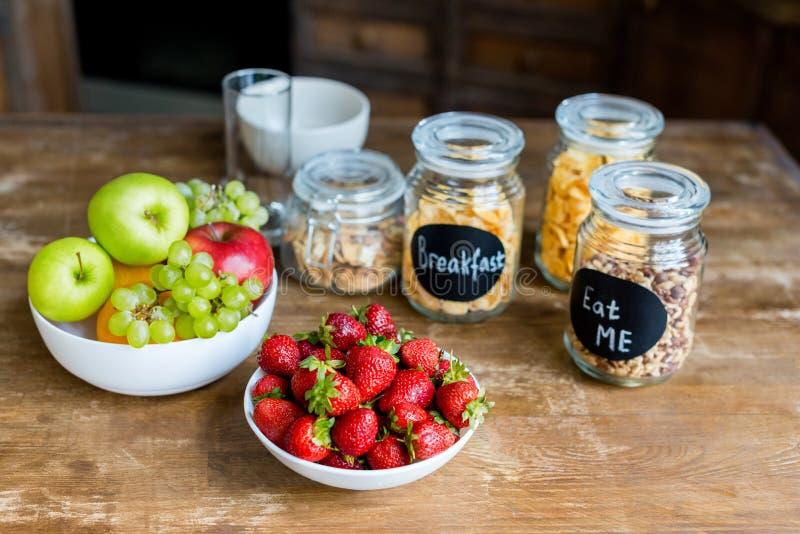 Großaufnahme von frischen reifen Früchten und von Getreide in den Glasgefäßen lizenzfreies stockbild
