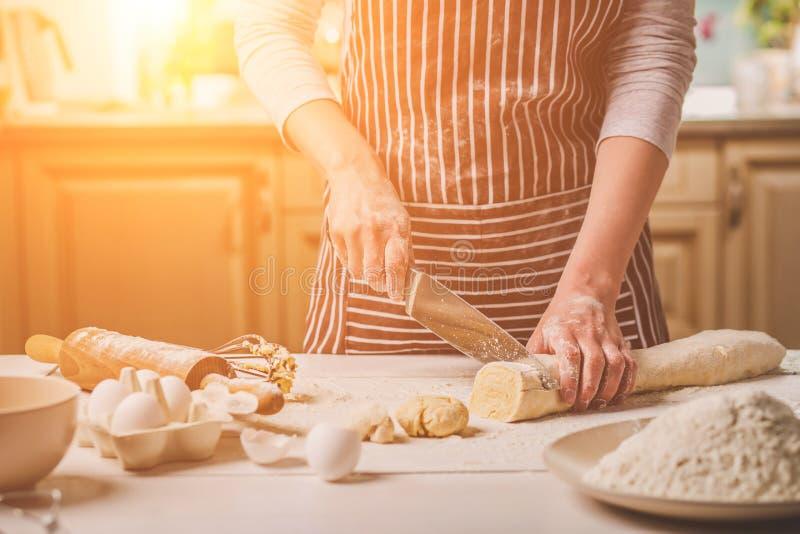 Großaufnahme von zwei Frau ` s Händen schnitt Messerteig lizenzfreies stockbild
