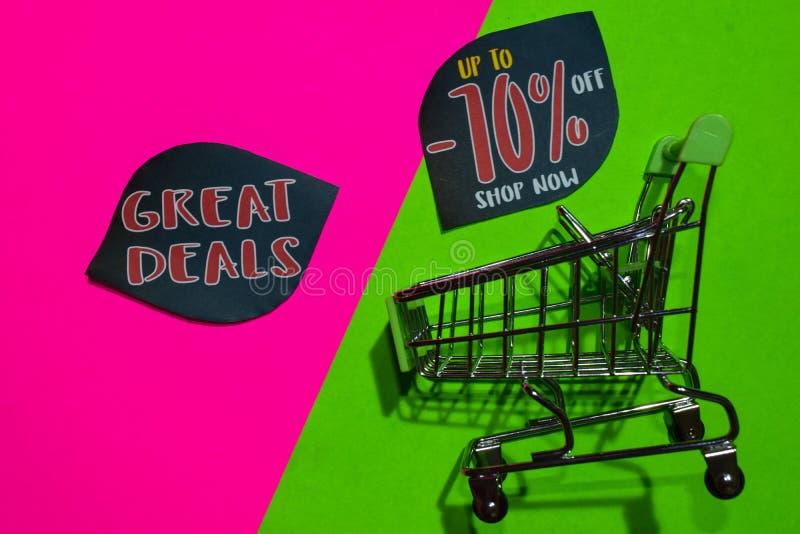Große Abkommen und bis -70% weg vom Geschäfts-jetzt Text und dem Einkaufswagen stockbild