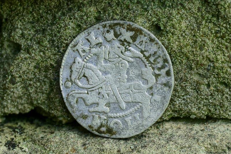 Große alte silberne mittelalterliche Münze nahe der Steinwand stockfotos