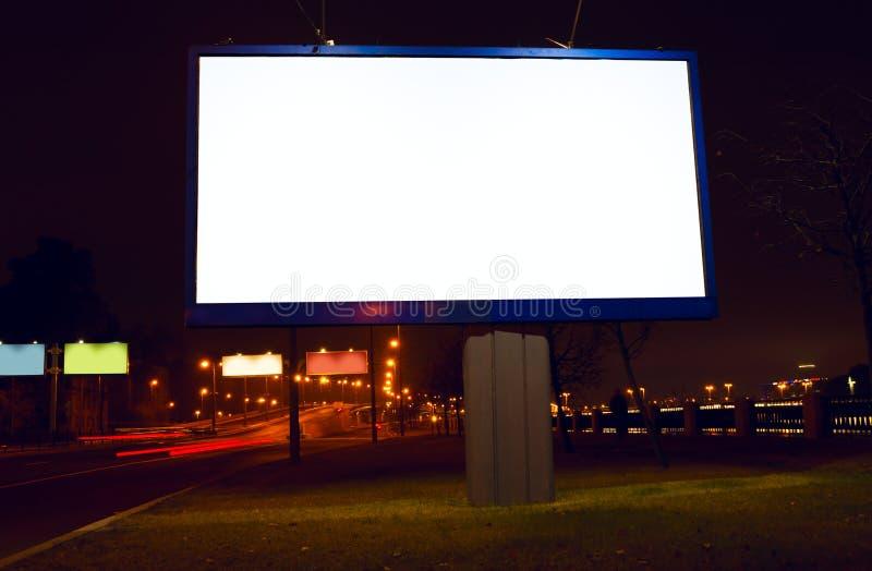 Große Anschlagtafel auf Nachtstraße stockfotos