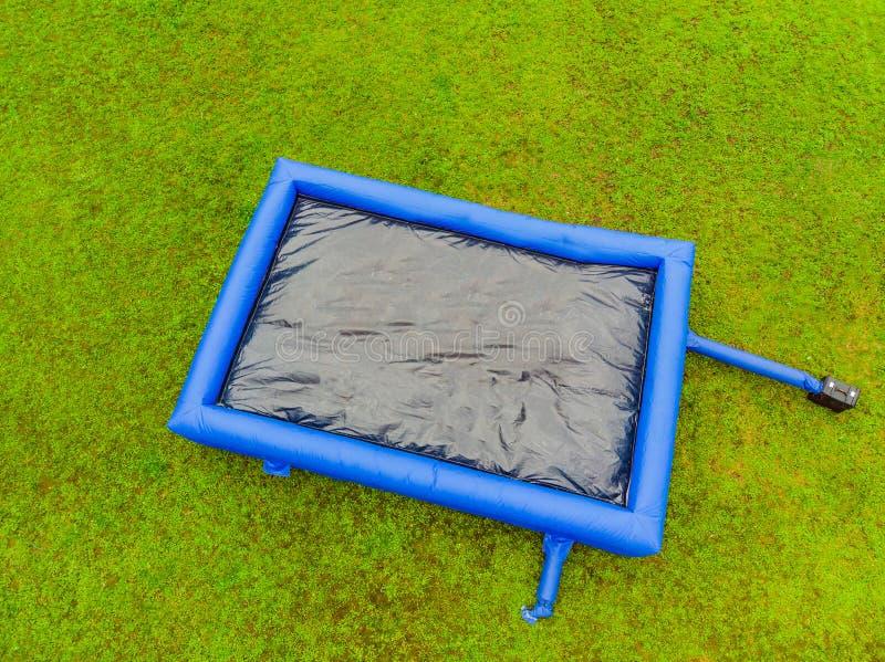 Große aufblasbare blaue Trampoline auf grünem Gras lizenzfreie stockbilder