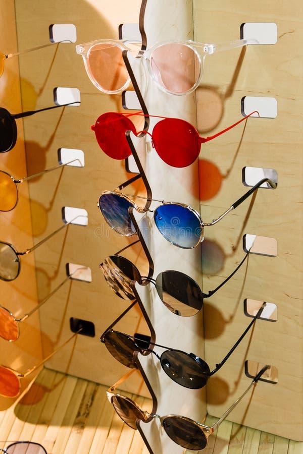 Große Auswahl der Sonnenbrille und der Gläser auf einem Stand stockfotografie