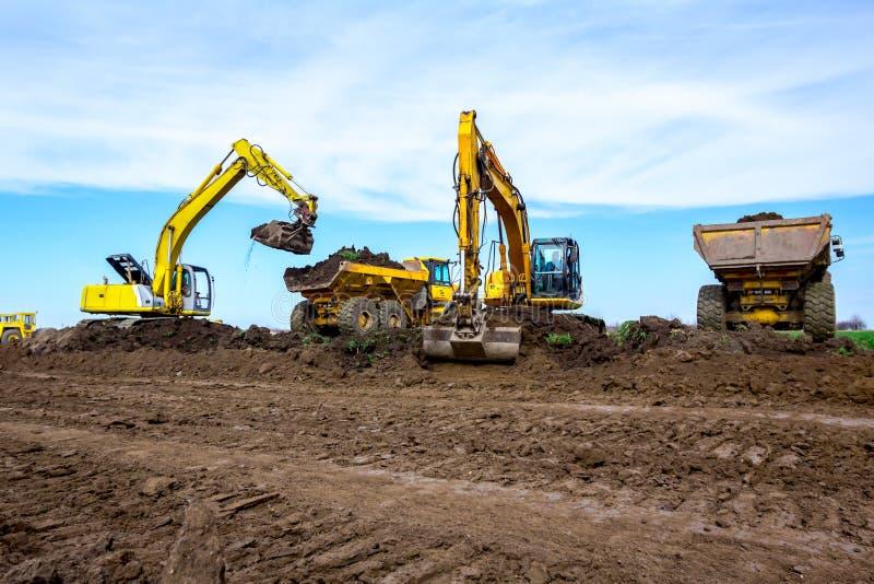 Große Bagger laden zwei LKWs mit Boden auf Baustelle stockbilder